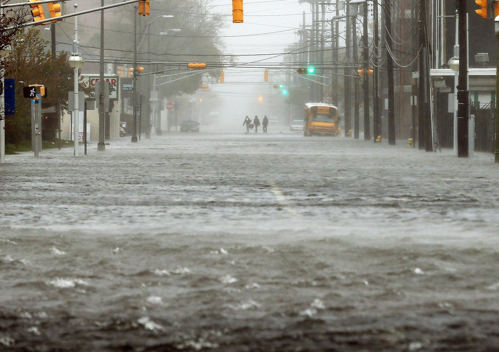 . People walk down a flooded street as Hurricane Sandy moves up the coast on October 29, 2012 in Atlantic City, New Jersey.  Governor Chris Christie\'s emergency declaration is shutting down the city\'s casinos and 30,000 residents were ordered to evacuate.   (Photo by Mario Tama/Getty Images)