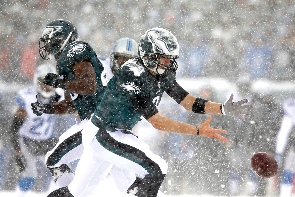 Description of . In the snow, Philadelphia Eagles' Nick Foles cannot hang onto the ball during the first half of an NFL football game against the Detroit Lions, Sunday, Dec. 8, 2013, in Philadelphia. (AP Photo/Michael Perez)