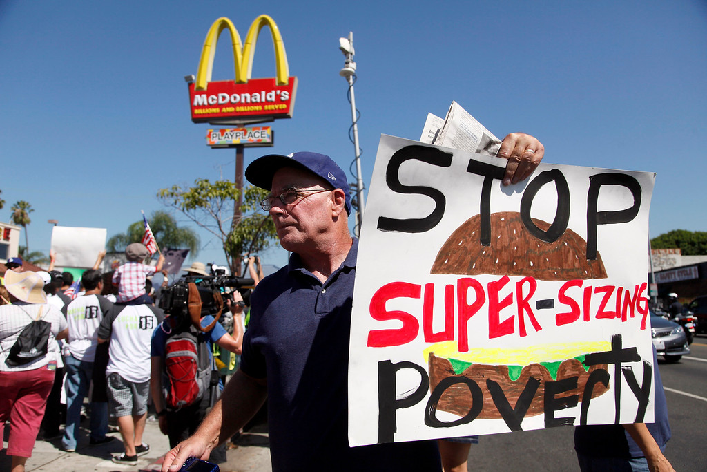Description of . Kevin Cole protests outside a fast food restaurant on Thursday Aug. 29, 2013 in Los Angeles. (AP Photo/Nick Ut)