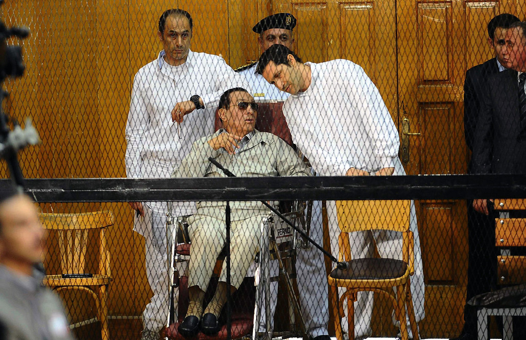 Description of . Egyptian toppled president Hosni Mubarak and his two sons Alaa, right, and Gamal stand behind bars during their trial at the Police Academy on September 14, 2013 in Cairo. Mubarak appeared in court for the second time since his release from Cairo's Tora prison and he faced an array of charges, including complicity in the deaths of some 850 people killed in the Arab Spring-inspired uprising against him, and corruption.   AHMED EL-MALKY/AFP/Getty Images