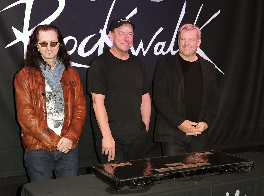 Description of . This Nov. 20, 2012 file photo shows members of the band Rush, from left, Geddy Lee, Neil Peart, and Alex Lifeson at the RockWalk induction of Rush at Guitar Center in Los Angeles. The eclectic group of rockers Rush and Heart, rappers Public Enemy, songwriter Randy Newman,