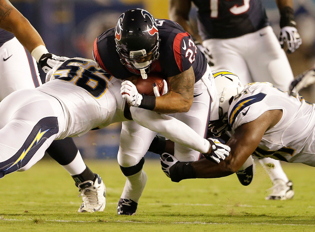 Description of . Houston Texans running back Arian Foster drives between San Diego Chargers inside linebacker Donald Butler, left, and defensive end Kendall Reyes during the first half of an NFL football game Monday, Sept. 9, 2013, in San Diego. (AP Photo/Gregory Bull)