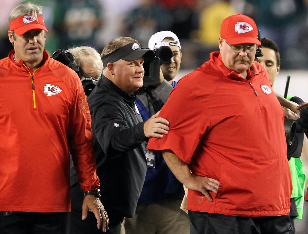 Description of . Philadelphia Eagles coach Chip Kelly, center,  reaches out to Kansas City Chiefs coach Andy Reid as they meet on the field before an NFL football game in Philadelphia on Thursday, Sept. 19, 2013. (AP Photo/Philadelphia Daily News, Yong Kim)