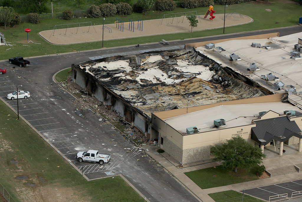 Description of . WEST, TX - APRIL 18:  An explosion yesterday at the West Fertilizer Company destroyed the West Intermediate School a block away, shown from the air on April 18, 2013 in West, Texas. According to West Mayor Tommy Muska, around 14 people, including 10 first responders, were killed and more than 150 people were injured when the fertilizer company caught fire and exploded, leaving damaged buildings for blocks in every direction.  (Photo by Chip Somodevilla/Getty Images)