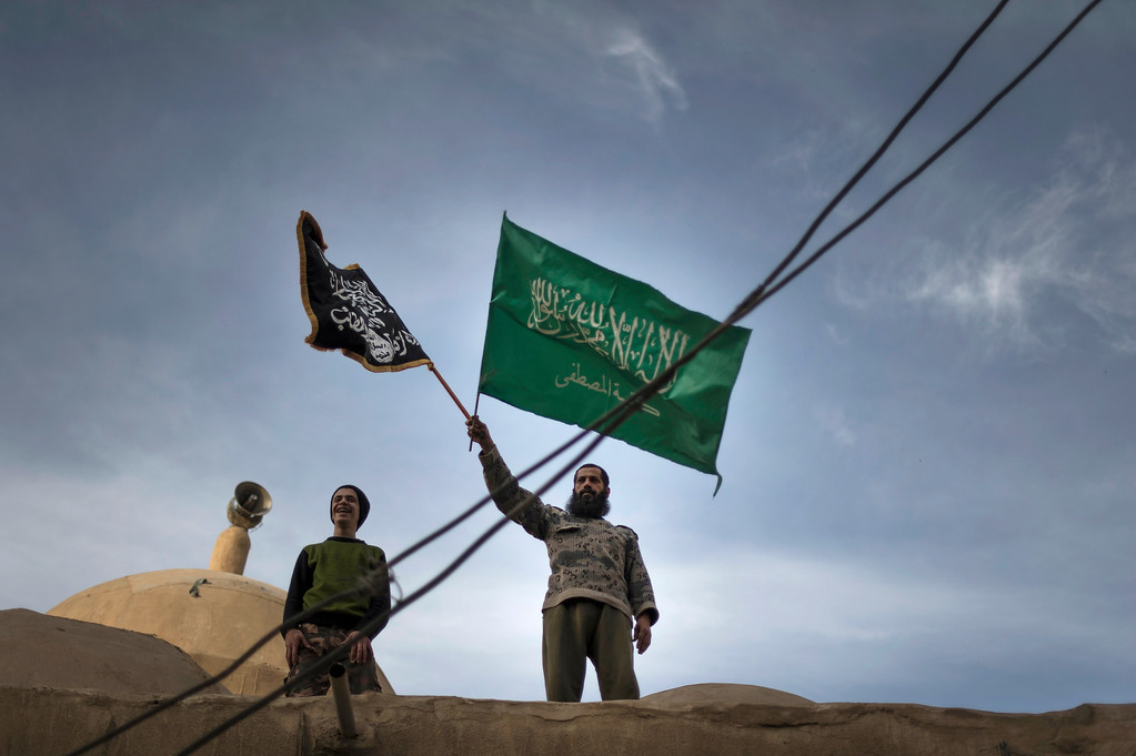Description of . Members of Liwa (brigade) Hamzah, a newly formed Islamist brigade from the Syrian eastern city of Deir Ezzor stand on top of a mosque holding the flags of Jebhat al-Nusra (L) and Katiba al-Mustafa, another Islamist unit hailing from Deir Ezzor, during a rally in the centre of the city to announce their formation on February 25, 2013. Syria's opposition and foreign powers hold crucial talks in Rome with Washington suggesting it is ready to boost support to rebels in their struggle against President Bashar al-Assad. ZAC BAILLIE/AFP/Getty Images