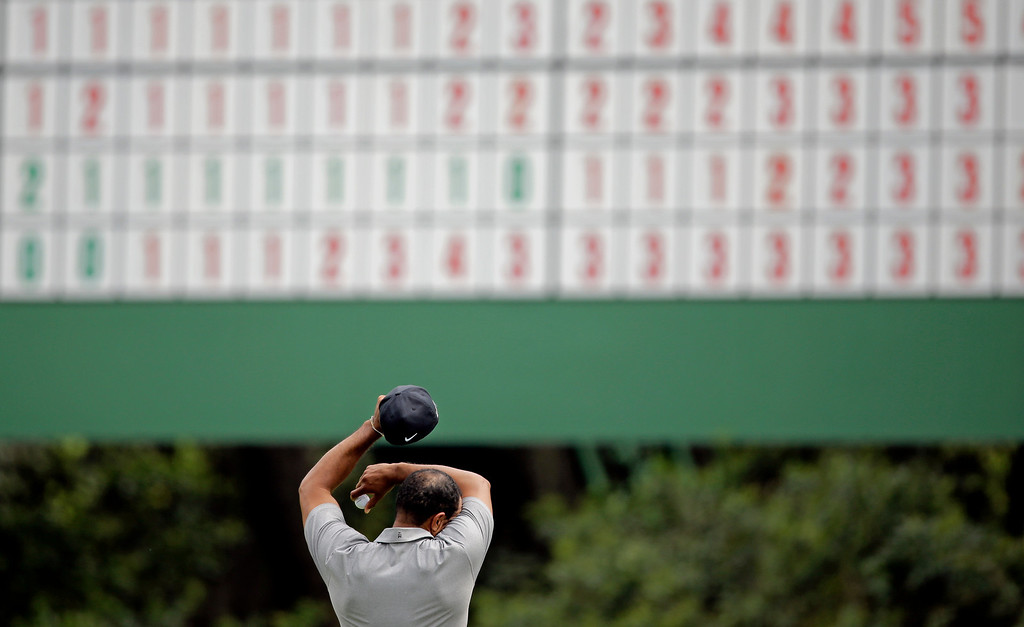 Description of . Tiger Woods wipes his forehead on the 11th green during the first round of the Masters golf tournament Thursday, April 11, 2013, in Augusta, Ga. (AP Photo/Matt Slocum)
