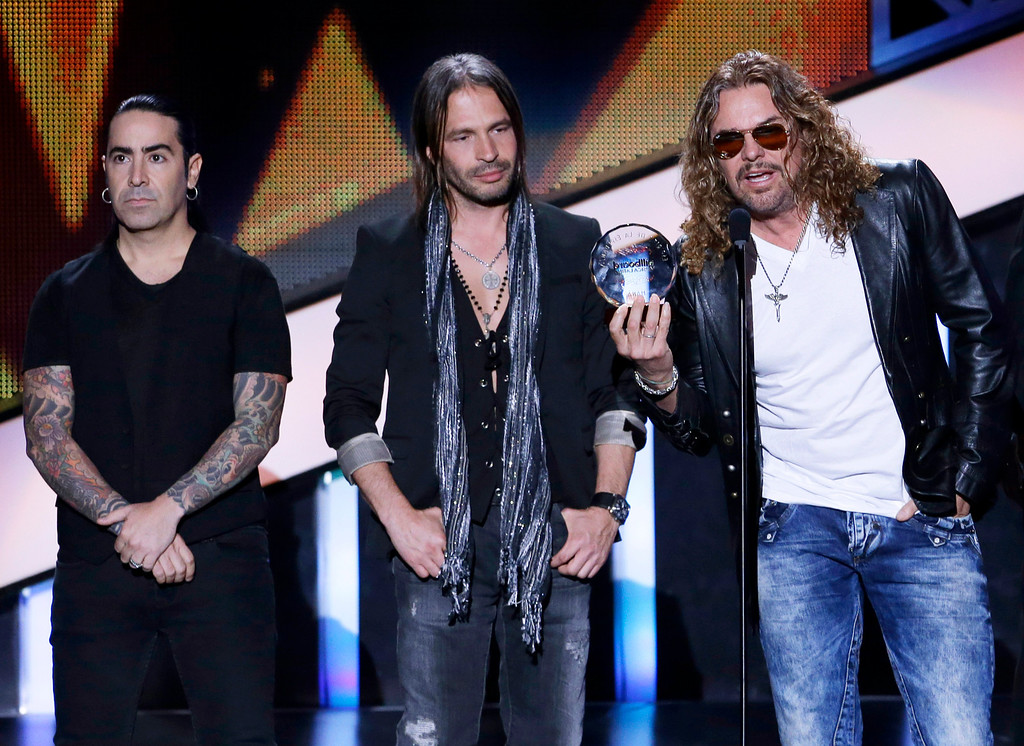 Description of . Members of the band Mana, from left, Alex Gonzalez, Sergio Vallin and Fher Olvera receive the Billboard Spirit of Hope Award at the Latin Billboard Awards in Coral Gables, Fla., Thursday April 25, 2013. (AP Photo/Alan Diaz)