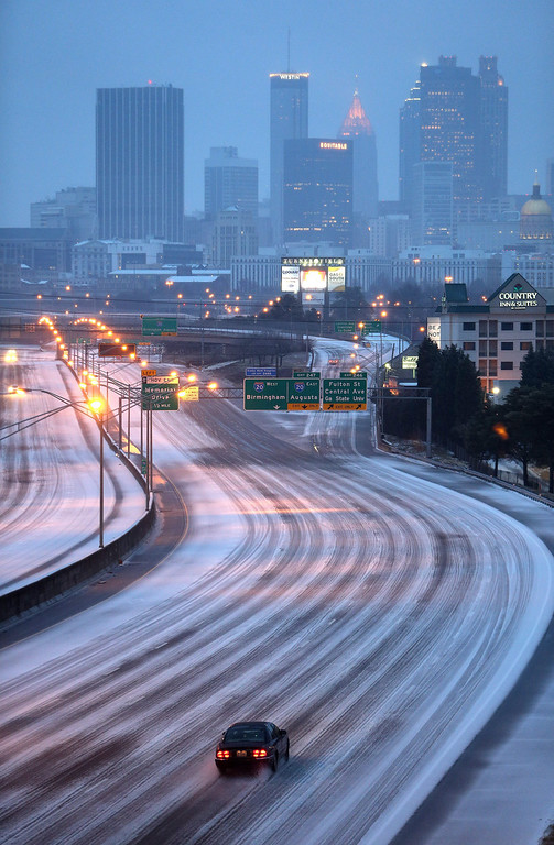 Description of . A lone car makes its way north on Interstate 75-85 just south of downtown Atlanta, Georgia, USA early 12 February 2014, as an ice storm moves through the area leaving a thick layer of slush on roadways.  EPA/BEN GRAY