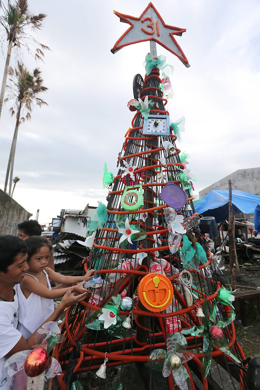 Description of . Filipino typhoon survivors Alejandro Guande, 41, and her daughter Alia, 3, arrange a giant Christmas tree in preparation for traditional Christmas dinner 'Noche Buena' outside a public school turned into a temporary evacuation center in the typhoon devastated city of Tacloban, Leyte Province, Philippines, 24 December 2013. Town officials have launched a contest for the best Christmas decoration among the villages in the city of Tacloban, with a first prize of some 1694 euros. The destruction and losses in lives and properties caused by Haiyan are casting a pall over the holiday season, in a country known for having the world's longest celebration of Christmas. According to the Philippine disaster relief agency, 6,102 people were killed and 1,779 were still missing from Haiyan's onslaught. The typhoon, the world's strongest on record, destroyed more than 1 million homes, key infrastructure and commercial establishments.  EPA/DENNIS M. SABANGAN