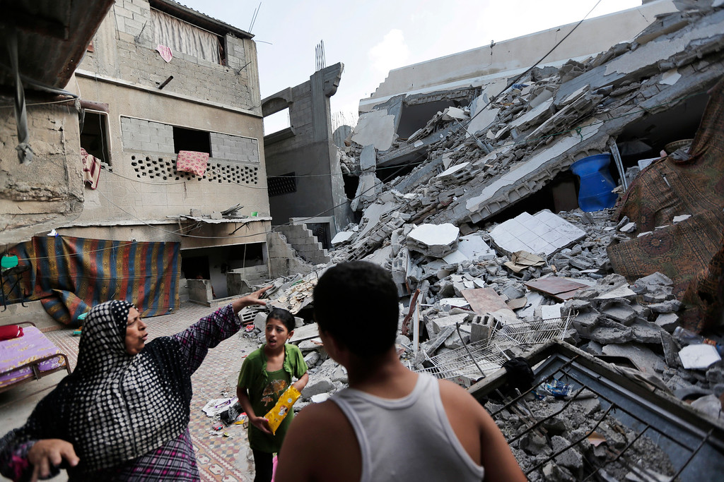 Description of . Palestinian Heygar Jendiyah, left, points to where the family house kitchen once stood, partially destroyed by an Israeli strike earlier during the war, as her children Ranin, 10, center, and Helmi, right, listen, in the Sabra neighborhood of Gaza City, northern Gaza Strip, Thursday, July 31, 2014. The building houses 21 members of the extended family, and now with several rooms destroyed, they try to go about their lives, without electricity and without running water for several hours a day. (AP Photo/Lefteris Pitarakis)