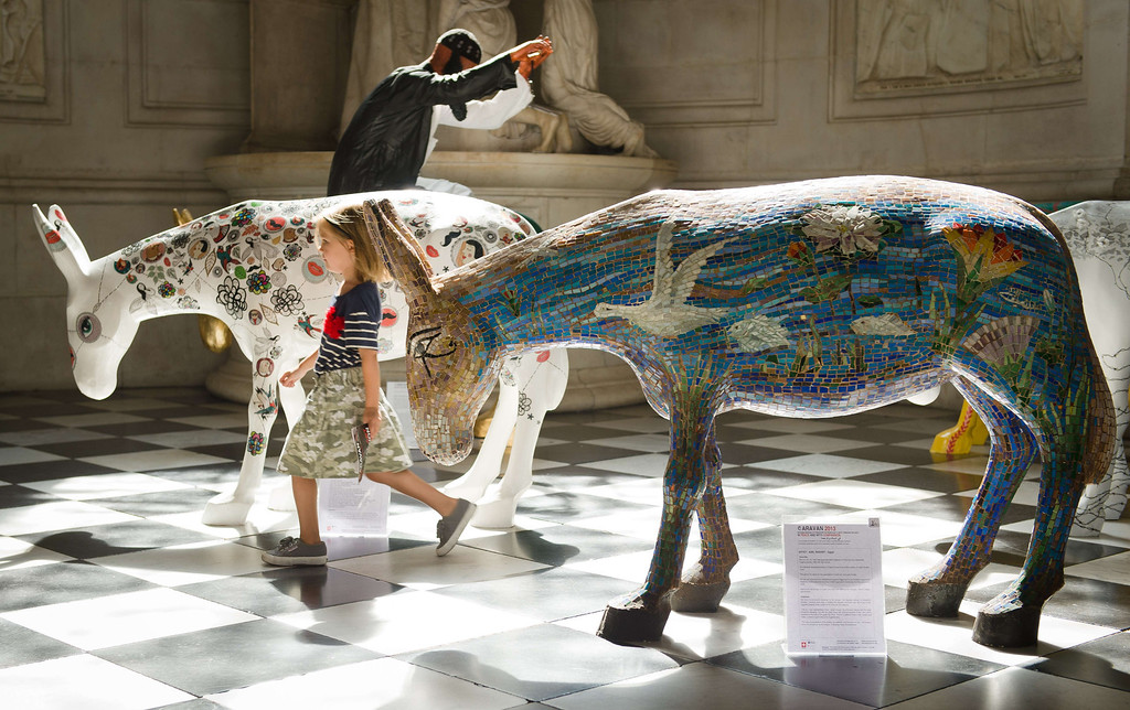 . A girl explores some of the 25 life-size painted donkeys, created by Egyptian and Western artists as they go on display in St Paul\'s Cathedral in London on August 30, 2013.     AFP PHOTO / LEON  NEAL/AFP/Getty Images