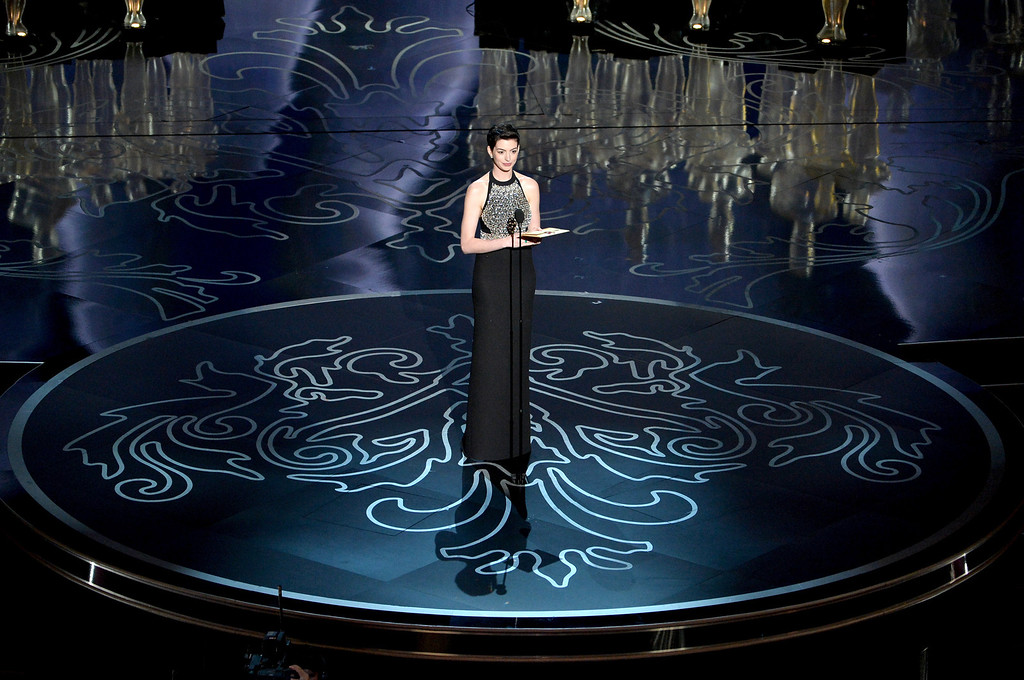 Description of . Actress Anne Hathaway speaks onstage during the Oscars at the Dolby Theatre on March 2, 2014 in Hollywood, California.  (Photo by Kevin Winter/Getty Images)