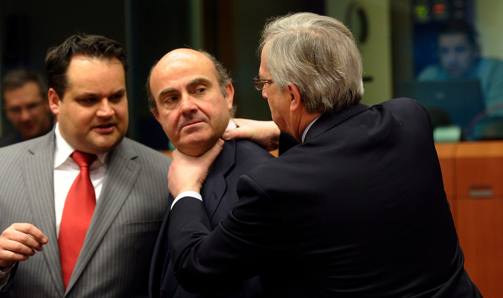 Description of . In this March 12, 2012 file photo, Luxembourg's Prime Minister Jean-Claude Juncker, right, puts his hands on the neck of Spain's Economy Minister Luis de Guindos, center, as Dutch Finance Minister Jan Kees De Jager, left, looks on during a meeting of eurozone finance ministers at the EU Council building in Brussels.  As ministers chatted with each other at the meeting, the eurogroup's chief, Jean-Claude Juncker, came up behind Spanish finance minister, Luis De Guindos, and jokingly grabbed him by the neck with both hands, but the gesture soon appeared to change into a laughing friendly greeting and then deep discussion.  The 17 euro countries were trying to focus on issues beyond the Greek crisis and deal with longer-term issues in their currency union, like discussing Spain's high deficits and potentially dangerous imbalances in some countries. (AP Photo/Virginia Mayo, File)