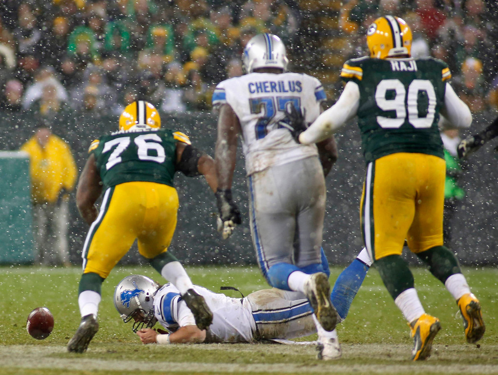 . Detroit Lions quarterback Matthew Stafford (C) fumbles the ball that is recovered and ran back for a touchdown by Green Bay Packers defensive end Mike Daniels (L) during the first half of a NFL football game in Green Bay, Wisconsin December 9, 2012. REUTERS/Darren Hauck