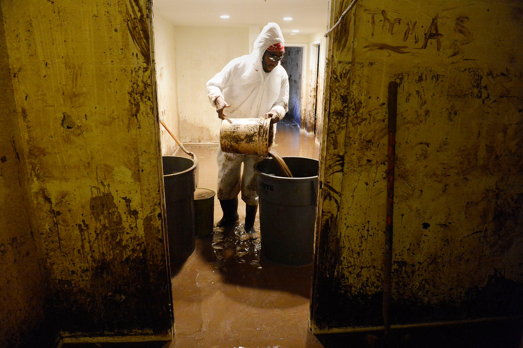 Description of . BOULDER, CO - SEPTEMBER 14: Worker, Kenny Horton, working for Burggraf Disaster Restoration, based out of Oklahoma, dumps a bucket of water into a large plastic trash can  from the basement of a home near Iris Ave and 9th St. in Boulder, Colorado on September 16, 2103. The basement was completely flooded out from the overflowing Two-Mile Creek. (Photo By Andy Cross/The Denver Post)