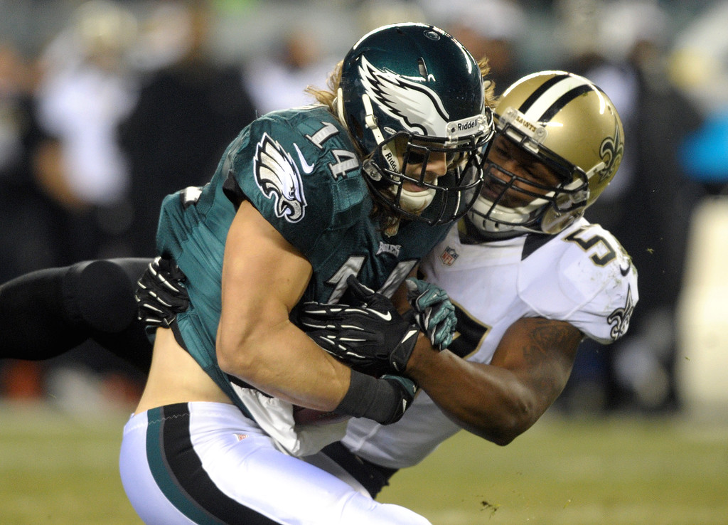 Description of . Philadelphia Eagles wide receiver Riley Cooper, left, is tackled by New Orleans Saints linebacker David Hawthorne after a reception during an NFL football wild-card playoff game Saturday, Jan. 4, 2014, in Philadelphia. The Saints won 26-24. (AP Photo/The Express-Times, Matt Smith)
