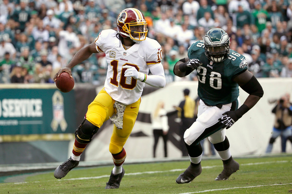 Description of . Washington Redskins quarterback Robert Griffin III, left, scrambles past Philadelphia Eagles nose tackle Bennie Logan during the first half of an NFL football game in Philadelphia, Sunday, Nov. 17, 2013. (AP Photo/Matt Slocum)