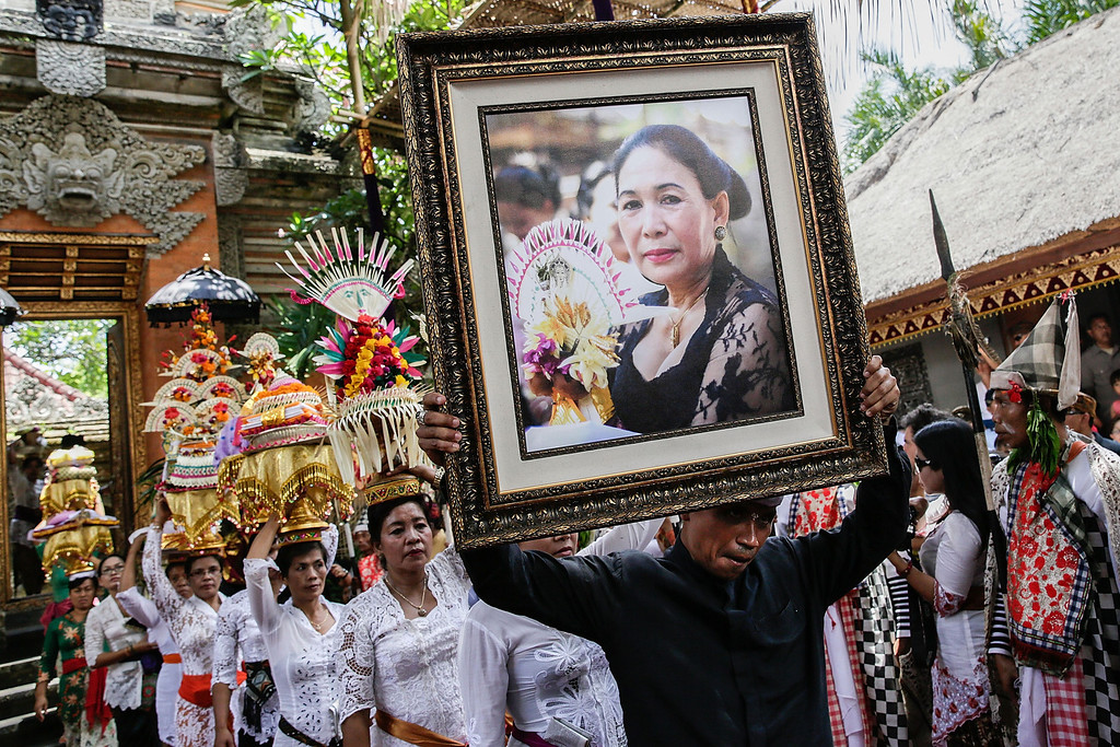 Description of . A relative holds the picture of Tjokorda Istri Sri Tjandrawati during the Royal cremation ceremony on November 1, 2013 in Ubud, Bali, Indonesia. (Photo by Agung Parameswara/Getty Images)