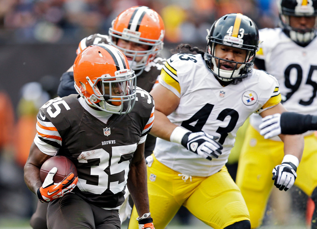 Description of . Cleveland Browns running back Fozzy Whittaker (35) runs against Pittsburgh Steelers safety Troy Polamalu (43) in the first quarter of an NFL football game Sunday, Nov. 24, 2013, in Cleveland. (AP Photo/Tony Dejak)