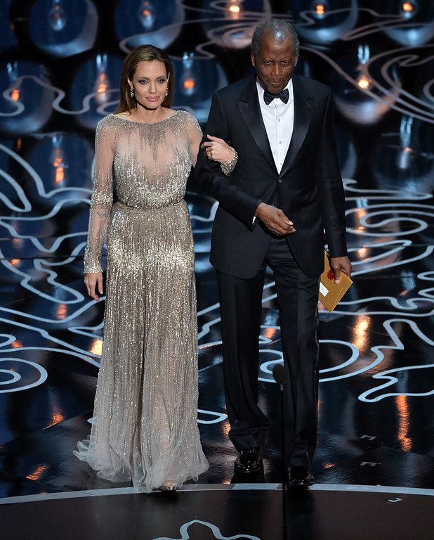 Description of . Actors Angelina Jolie (L) and Sidney Poitier walk onstage during the Oscars at the Dolby Theatre on March 2, 2014 in Hollywood, California.  (Photo by Kevin Winter/Getty Images)