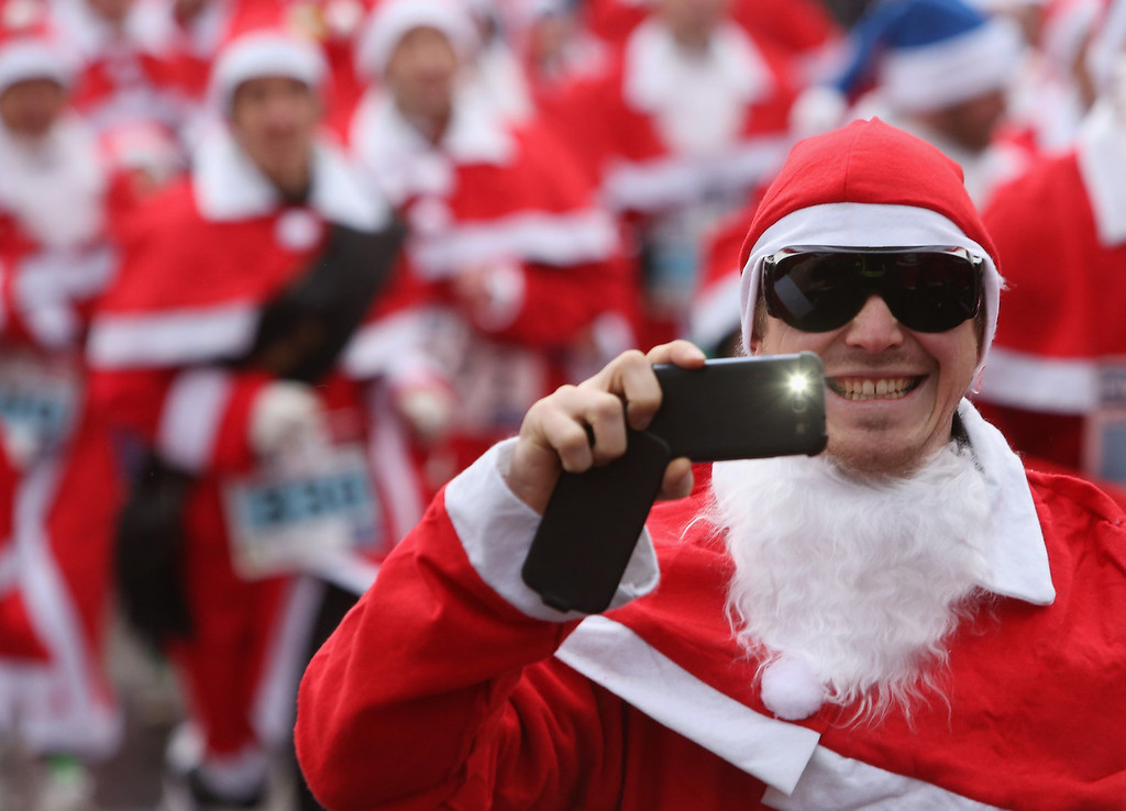 Description of . A participant takes a photo with a mobile phone as he runs in the 5th annual Michendorf Santa Run (Michendorfer Nikolauslauf) on December 8, 2013 in Michendorf, Germany. Over 900 people took part in this year's races, which included one for children and one for adults.  (Photo by Adam Berry/Getty Images)