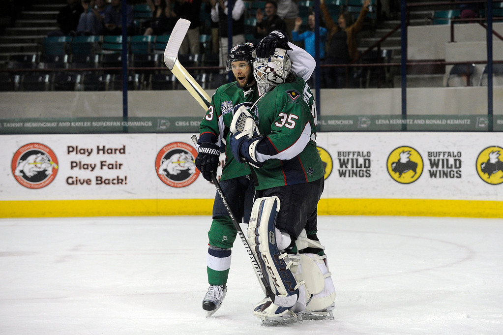 Description of . DENVER, CO - MAY 2: TJ Fox (13) of the Denver Cutthroats congratulates Denver Cutthroats goalie Kent Patterson (35) as time expires on the third period of game 1 of the Ray Miron Presidents Cup Finals at the Denver Coliseum in Denver, Colorado on May 2, 2014. (Photo by Seth McConnell/The Denver Post)