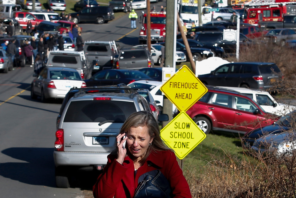 Description of . A woman mourns while speaking on the phone near Sandy Hook Elementary School, where a gunman opened fire on school children and staff in Newtown, Connecticut on December 14, 2012. A heavily armed gunman opened fire on school children and staff at a Connecticut elementary school on Friday, killing at least 26 people, including 18 children, in the latest in a series of shooting rampages that have tormented the United States this year.     REUTERS/Adrees Latif