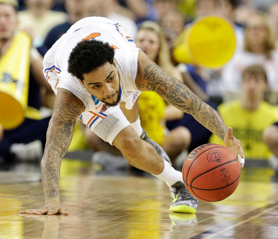 Description of . Florida\'s Mike Rosario (3) grabs a loose ball against Michigan  during the first half of a regional final game in the NCAA college basketball tournament, Sunday, March 31, 2013, in Arlington, Texas. (AP Photo/Tony Gutierrez)