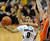 Askia Booker of CU dishes off as Olaf Schaftnaar of OSU during the second half of the March 9, 2013 game in Boulder.    (Cliff Grassmick/Boulder Daily Camera)