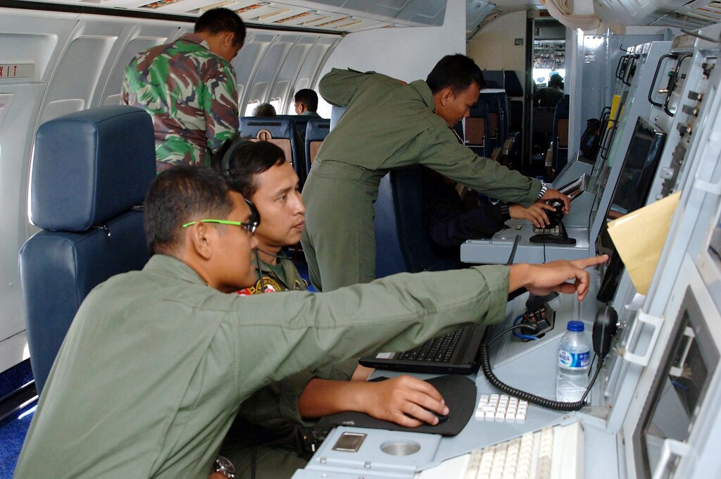 Description of . A handout photo released by the Indonesian Air force shows air force personnel during a search mission for a Malaysian Airlines aircraft on board of a military surveillance airplane over the Malacca straits, 12 March 2014. The search for missing Malaysia Airlines flight MH370 was expanded, including more areas that were not on its flight path. Nearly 100 vessels and aircraft from 10 countries in Asia and the Pacific, including Malaysia, were scouring the South China Sea to locate the Boeing 777-200 that disappeared on en route to Beijing from Kuala Lumpur on 08 March.  EPA/INDONESIAN AIRFORCE /