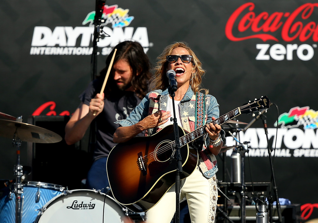 Description of . DAYTONA BEACH, FL - JULY 06:  Sheryl Crow performs prior to the NASCAR Sprint Cup Series Coke Zero 400 at Daytona International Speedway on July 6, 2013 in Daytona Beach, Florida.  (Photo by Mike Ehrmann/Getty Images)