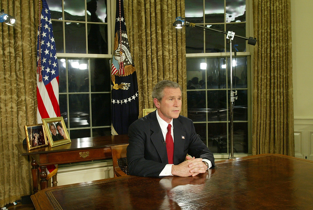 "Description of . U.S. President George W. Bush addresses the nation March 19, 2003 in the Oval Office of the White House in Washington, DC. Bush announced that the U.S. military struck at ""targets of opportunity\"" in Iraq. Air defense sirens and anti-aircraft fire was reported briefly in Baghdad. (Photo by Alex Wong/Getty Images)"