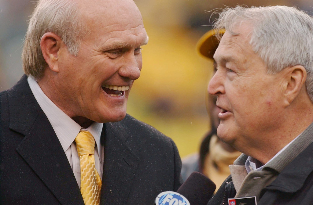 Description of . Pittsburgh Steelers Hall of Fame quarterback Terry Bradshaw, left, and former coach Chuck Noll chat before the Steelers game against the St. Louis Rams, Sunday, Oct. 26, 2003, in Pittsburgh. The two were among other former Steelers greats who took part in a celebration in honor of the Steelers playing the 1000th game in their history Sunday. The Steelers lost to the Rams, 33-21. (AP Photo/Carolyn Kaster)