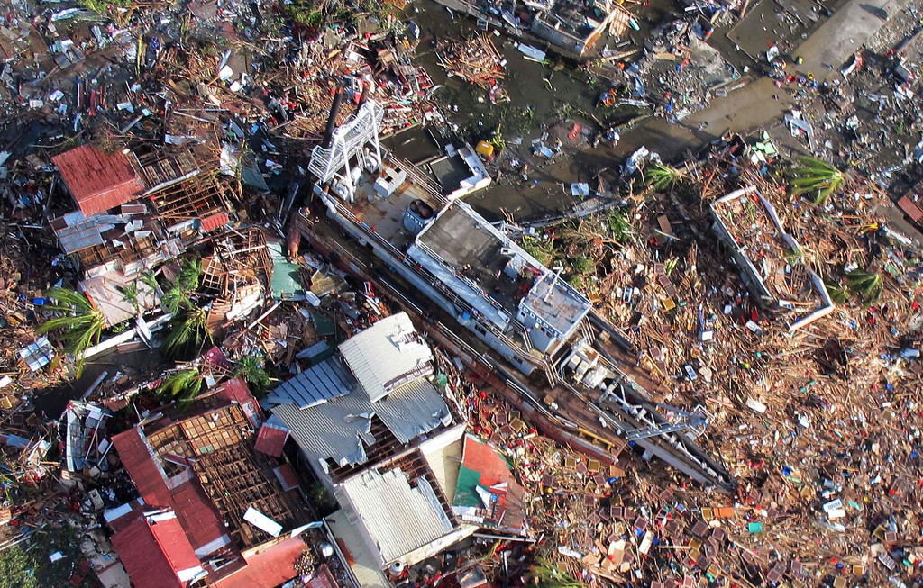 Description of . In this aerial photo taken on Saturday, Nov. 9, 2013, and released by the Philippine Air Force, a ferry boat is seen washed inland from a massive storm surge caused by Typhoon Haiyan, in the city of Tacloban, central Philippines. Typhoon Haiyan, one of the strongest storms on record, slammed into six central Philippine islands on Friday leaving a wide swath of destruction and thousands of people dead. (AP Photo/Philippines Air Force)