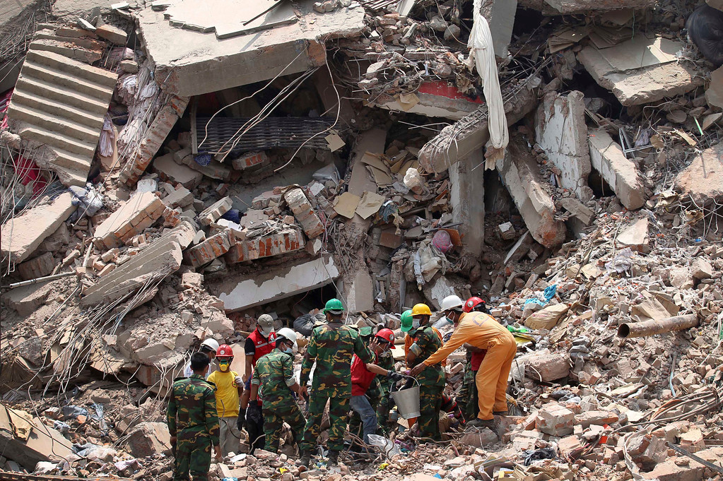 Description of . Workers try to release two bodies trapped in the rubble of collapsed Rana Plaza garment factory building in Savar, near Dhaka, Bangladesh, April 30, 2013. The collapse of Rana Plaza in Dhaka that killed 1,129 people.  (AP Photo/Wong Maye-E, File)