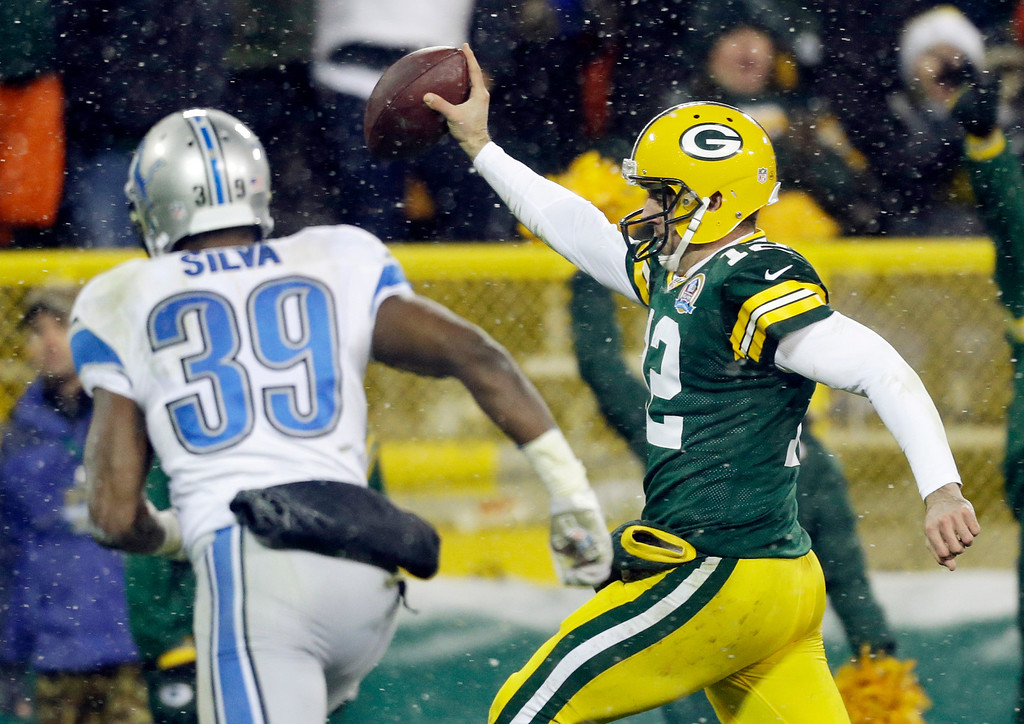 Description of . Green Bay Packers quarterback Aaron Rodgers breaks away from Detroit Lions' Ricardo Silva (39) for a 27-yard touchdown run during the second half of an NFL football game Sunday, Dec. 9, 2012, in Green Bay, Wis. (AP Photo/Jeffrey Phelps)