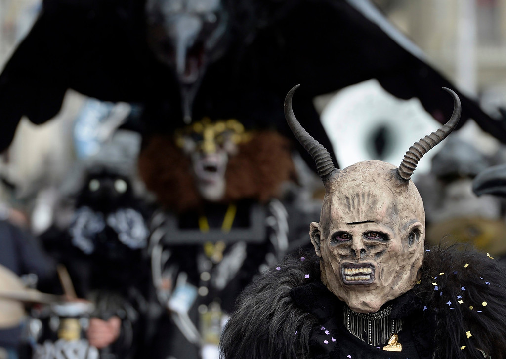 Description of . Masked revelers parade through the streets during the start of the carnival season in Lucerne, Switzerland, 27 February 2014.  EPA/URS FLUEELER