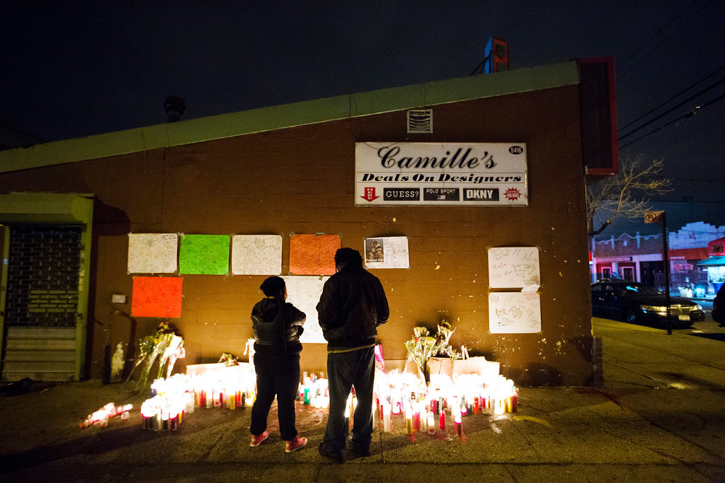 Description of . Mourners stand by a memorial for 16-year-old Kimani
