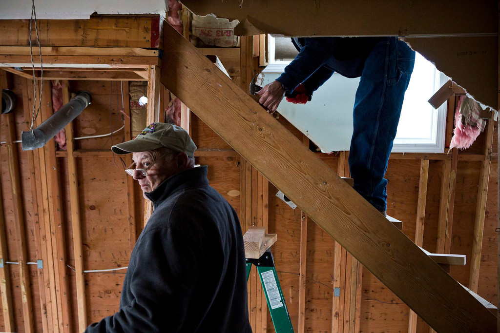 Description of . Paul Lynch, a contractor, helps repair a home he built 23 years ago, that was damaged by Hurricane Sandy, in the Ortley Beach area of Toms River, New Jersey November 28, 2012. The storm made landfall along the New Jersey coastline on October 29, 2012 - one month ago tomorrow. REUTERS/Andrew Burton