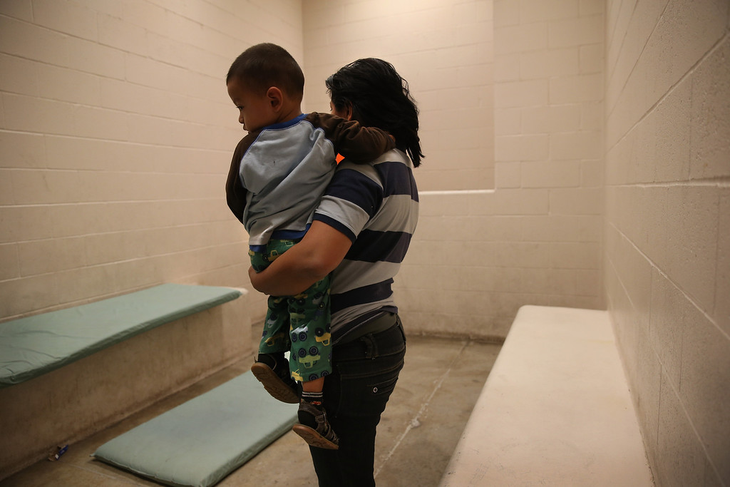 Description of . MCALLEN, TX - APRIL 11:  A Honduran mother holds her toddler son at the U.S. Border Patrol detainee processing center on April 11, 2013 in McAllen, Texas. They had been caught by the Border Patrol while crossing illegally from Mexico into Texas. According to the Border Patrol, undocumented immigrant crossings have increased more than 50 percent in Texas\' Rio Grande Valley sector in the last year. With more apprehensions, they have struggled to deal with overcrowding while undocumented immigrants are processed for deportation. (Photo by John Moore/Getty Images)