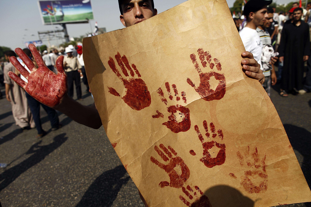 Description of . A supporter of the Muslim Brotherhood and ousted Egyptian president Mohamed Morsi shows his blood-stained hand while holding a placard bearing handprints made with the blood of victims who were shot during a gun battle outside the Cairo headquarters of the Republican Guard on July 5, 2013. At least three supporters of Morsi were killed and many others were wounded as they gathered for a protest, an AFP correspondent said. Shooting could be heard coming from both the Republican Guard and the ranks of the protesters. MAHMOUD KHALED/AFP/Getty Images