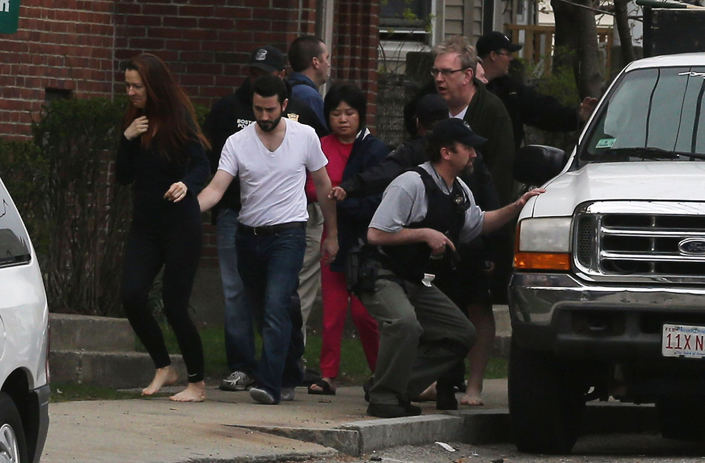 Description of . People are evacuated from a home near to a home police thought the one remaining suspect might have been hiding on April 19, 2013 in Watertown, Massachusetts.  (Photo by Mario Tama/Getty Images)