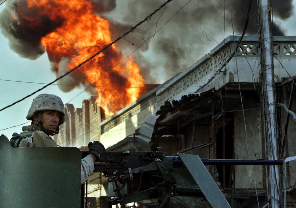 Description of . A U.S. Marine of the first Division passes by a burning house in the western part of Fallujah, Iraq, Sunday, Nov. 14, 2004. U.S. military officials said that U.S. Forces had now