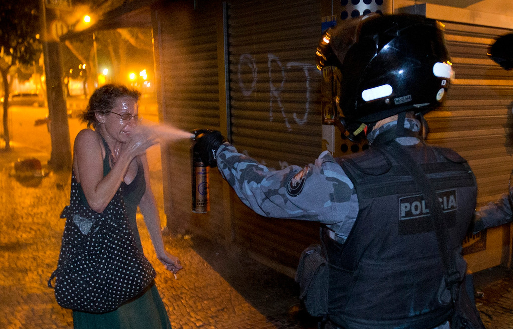 Description of . A military police pePper sprays a protester during a demonstration in Rio de Janeiro, Brazil, Monday, June 17, 2013. Protesters massed in at least seven Brazilian cities Monday for another round of demonstrations voicing disgruntlement about life in the country, raising questions about security during big events like the current Confederations Cup and a papal visit next month. ((AP Photo/Victor R. Caivano)