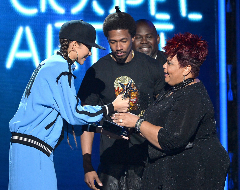 Description of . Singer Tamela Mann (R) accepts Best Gospel Artist from actress Zendaya (L) and TV personality Nick Cannon (C) onstage during the BET AWARDS '14 at Nokia Theatre L.A. LIVE on June 29, 2014 in Los Angeles, California.  (Photo by Kevin Winter/Getty Images for BET)