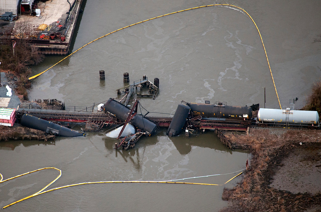 Description of . Several cars lay in the water after a freight train derailed in Paulsboro, N.J., Friday, Nov. 30, 2012. People in three southern New Jersey towns were told Friday to stay inside after the freight train derailed and several tanker cars carrying hazardous materials toppled from a bridge and into a creek. (AP Photo/Cliff Owen)