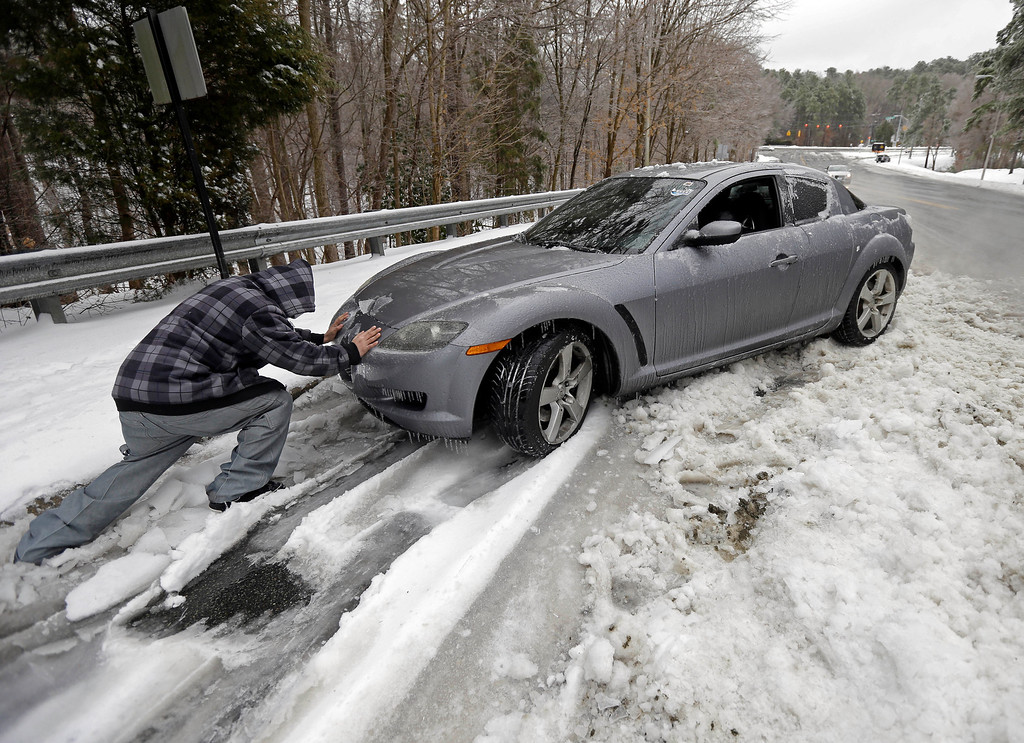 Description of . Passerby Leo Cruz helps push a car from the frozen roadside in Chapel Hill, N.C., Thursday, Feb. 13, 2014. The owner abandoned the car overnight during the storm. The National Weather Service issued a winter storm warning lasting into Thursday covering 95 of the state\'s 100 counties. (AP Photo/Gerry Broome)