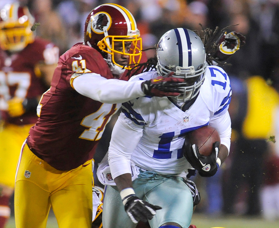 . Washington Redskins free safety Madieu Williams (41) tackles Dallas Cowboys wide receiver Dwayne Harris (17) during the first half of an NFL football game Sunday, Dec. 30, 2012, in Landover, Md. (AP Photo/Richard Lipski)