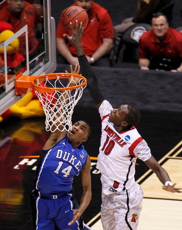Description of . Louisville Cardinals center Gorgui Dieng (10) blocks a shot by Duke Blue Devils guard Rasheed Sulaimon (14) in the first half during their Midwest Regional NCAA men's basketball game in Indianapolis, Indiana, March 31, 2013. REUTERS/John Sommers II