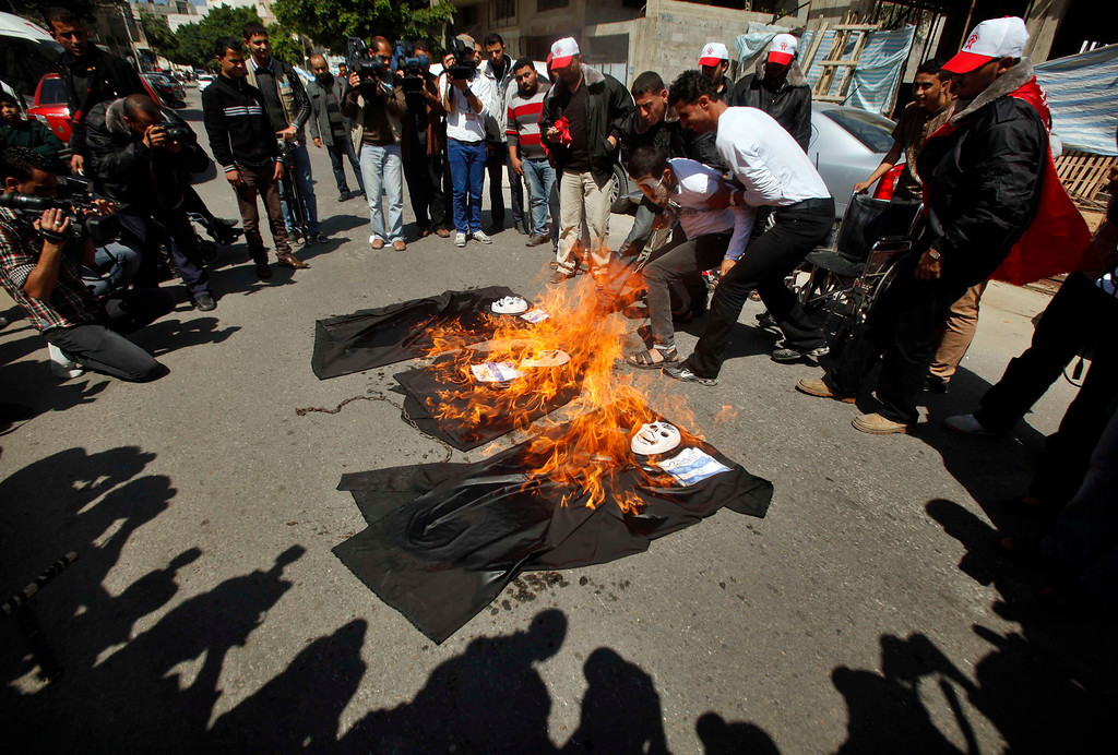 Description of . Palestinians burn models of Israeli soldiers depicted as ghosts during a protest against the visit of U.S. President Barack Obama, in Gaza City March 20, 2013. U.S.  REUTERS/Mohammed Salem